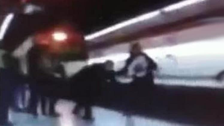 policia empujado a la via de tren